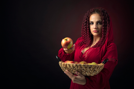 Portrait of attractive young woman in a fancy red dress with basket of apples. Girl with red wavy hair and makeup. Copy space.