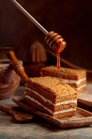 Homemade layered honey cake with cream on a old wooden table.