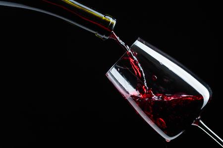 Rotwein wird auf schwarzem Hintergrund in Weinglas gegossen.