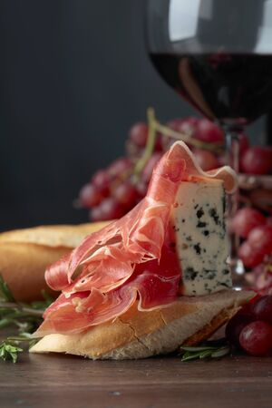 Sandwich with prosciutto, blue cheese and rosemary on a dark background. Delicious snack and red wine. Copy space for your text.