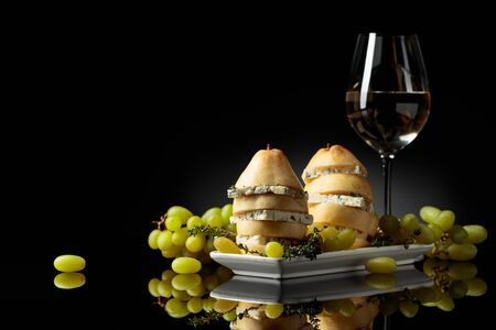 Blue cheese and white wine. Cheese with pear, thyme and grapes on a black reflective background. Copy space.