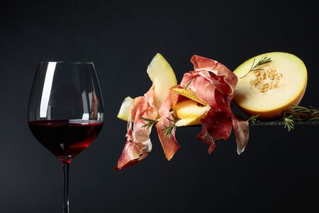 Glass of red wine and mediterranean snacks. Prosciutto with melon and rosemary on a black background, copy space. Фото со стока