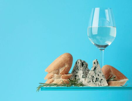 Blue cheese with bread, white wine and rosemary on a blue background. Copy space for your text.