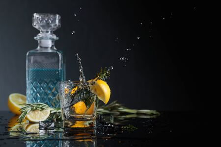 Gin-tonic with lemon slices and twigs of rosemary. Lemon slice falls into the glass. Copy space. 스톡 콘텐츠