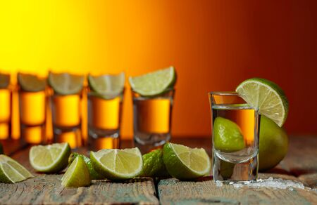 Tequila with sea salt and lime on a old wooden background. Copy space.