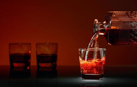 Pouring whiskey or scotch into glass. Alcoholic drink pouring from a decanter into a glass. Copy space.