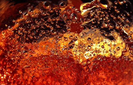 Alcoholic drink on a dark background, abstract splashing. Macro shot.