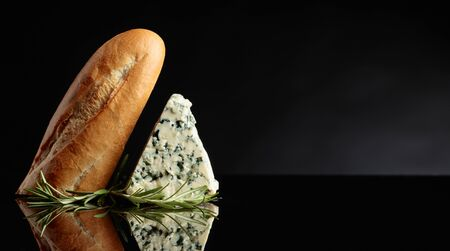Blue cheese with bread and rosemary on a black background. Copy space for your text.