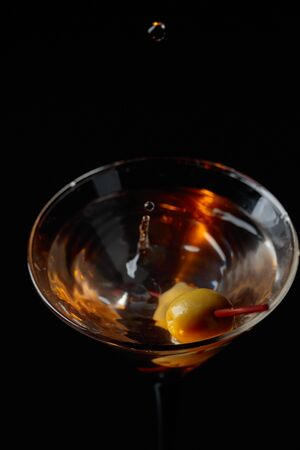 Martini cocktail with green olives on a black background. Copy space. Foto de archivo