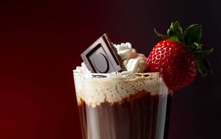 Chocolate drink with whipped cream, strawberry and pieces of black chocolate on a dark background. Copy space. 版權商用圖片