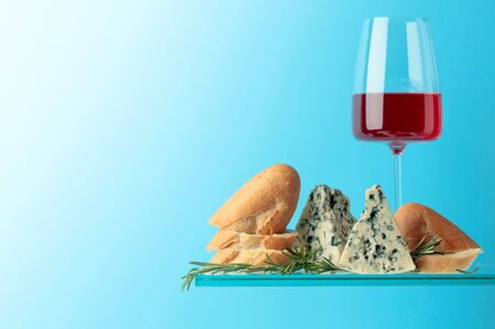 Blue cheese with bread, pink wine and rosemary on a blue background. Copy space for text.