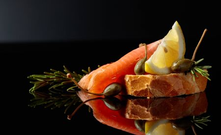 Sandwich with trout fillets, lemon slice, capers and rosemary on a black reflective background. Copy space.