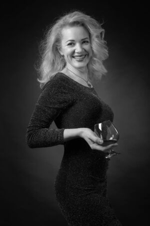 Attractive happy mature woman in a black evening dress with lurex holding a glass of brandy. Beautiful forty years blonde with long hair on a black background.