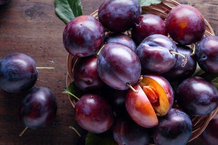 Ripe juicy plums on a old wooden table. Top view, copy space.
