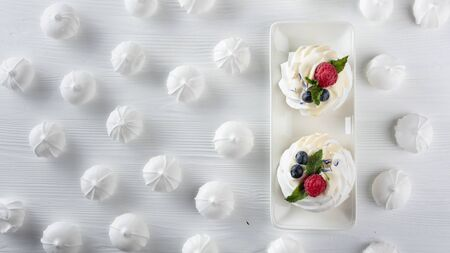 Dessert Pavlova with raspberries, blueberries and mint on a white wooden table. Top view.