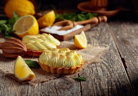 Törtchen mit Zitronencreme und Minze auf einem alten Holztisch. Hausgemachte Desserts mit Zutaten und Küchenutensilien aus Holz.
