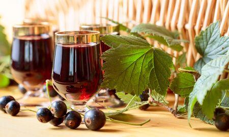 Domowy likier z czarnej porzeczki i świeże jagody, drewniane tła. Zdjęcie Seryjne