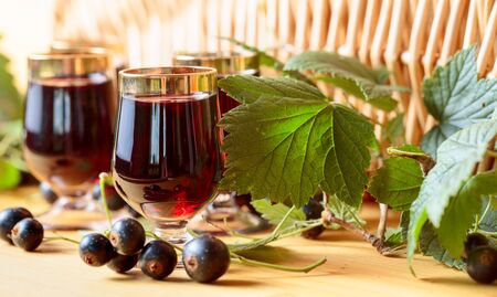 Homemade black currant liqueur and fresh berries, wooden background. Stock Photo
