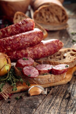 Rohwurst mit Thymian, Zwiebel, Knoblauch und Pfeffer. Wurst mit Brot und Gewürzen auf einem alten Holztisch.