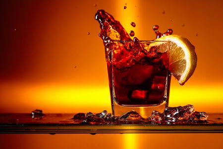 Slice of lemon falling into a glass of Cola. Cocktail with lemon. Copy space.