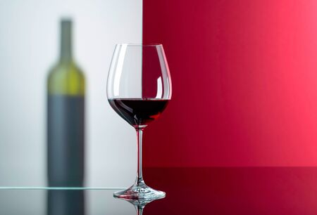 Bottle and glass of red wine on a black reflective background. Free space for text. Focus on foreground.
