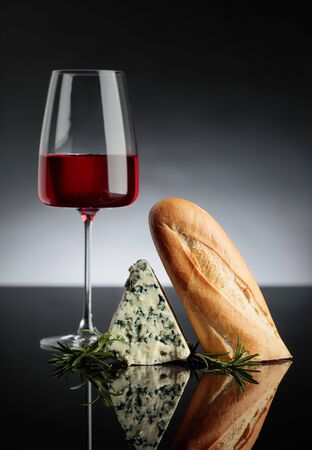 Blue cheese with bread, rosemary and pink wine on a black reflective background. Copy space for your text.