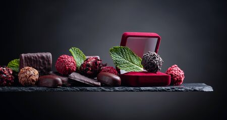 Various chocolates with mint leaves on a black background. Copy space.
