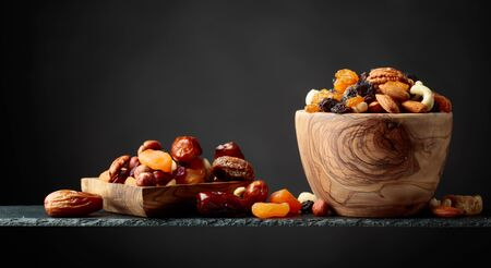 Dried fruits and nuts in wooden dish. Copy space.