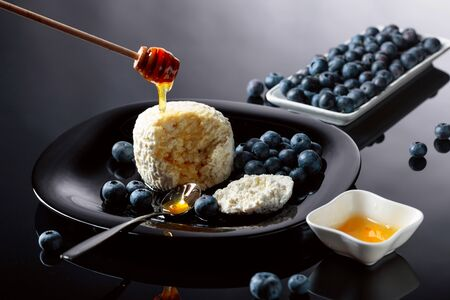 Cottage cheese with honey and blueberry on a black background.