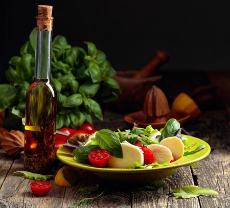 Green salad with mozzarella, tomato and basil in green plate on a old wooden table.
