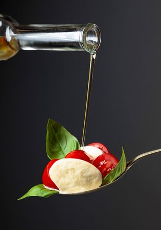 Mozzarella with tomato, basil and olive oil on a dark background. Copy space.