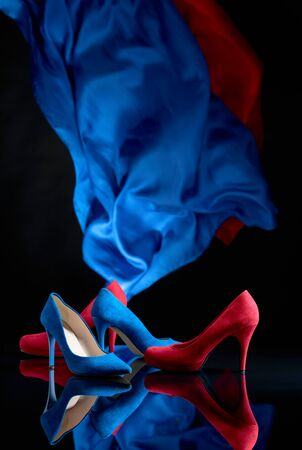 Blue and red womens corduroy shoes on a black reflective background. Copy space.