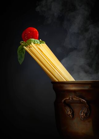 Raw spaghetti with tomato and basil in old brass pan. Black background. Copy space.