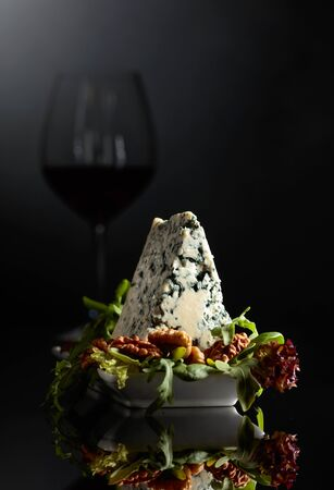 Blue cheese with walnuts and greens on a black background. In the background, the silhouette of a glass of red wine.