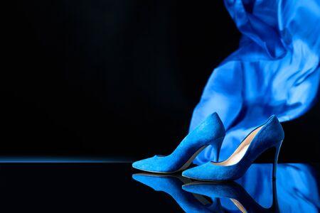 Blaue Damenschuhe aus Cord auf schwarzem, reflektierenden Hintergrund. Platz kopieren. Standard-Bild