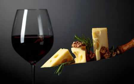Maasdam cheese with walnuts, rosemary and red wine on a dark background. Copy space. Фото со стока