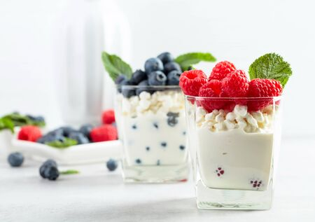 Dessert. Cottage cheese with cream, raspberry and blueberry garnished with fresh mint. Фото со стока