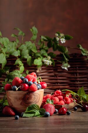 Berries closeup colorful assorted mix of strawberry, blueberry, raspberry and sweet cherry on a old wooden table in garden. Various juicy berries with leaves. Фото со стока