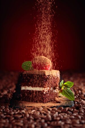 Chocolate cake with raspberry and mint. Coffee beans on a wooden table.