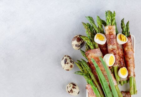 Green asparagus wrapped in bacon with boiled quail eggs. Top view. Фото со стока