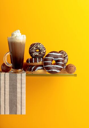Chocolate donuts and coffeel with cream on a yellow background.