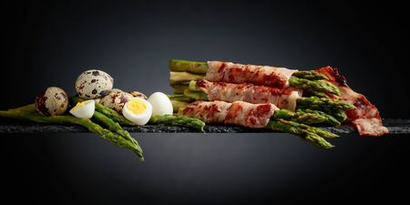 Green asparagus wrapped in bacon with boiled quail eggs.