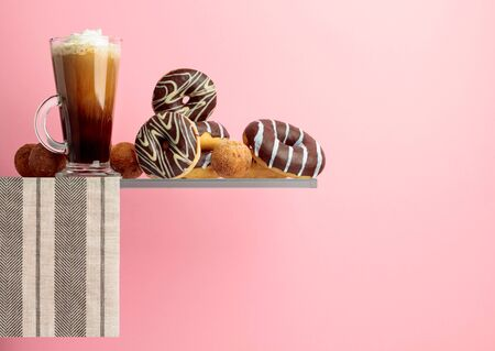 Chocolate donuts and coffee with cream on a pink background. Фото со стока