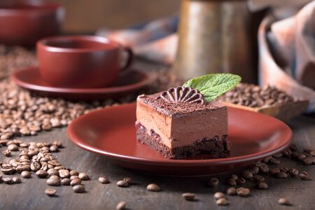 Chocolate cake with mint on a brown plate. Coffee beans on a wooden table.