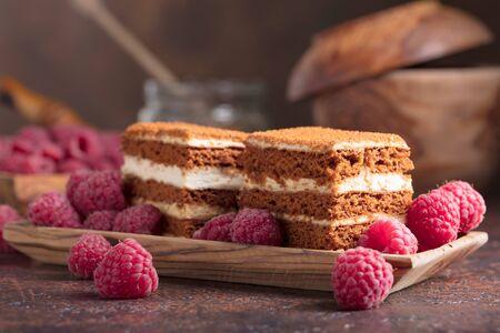 Layered honey cake with cream and  raspberries. Фото со стока
