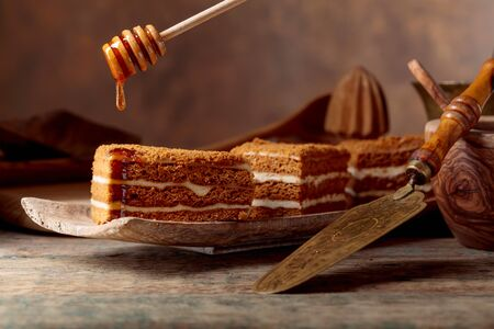 Layered honey cake with cream and honey on a old wooden table.