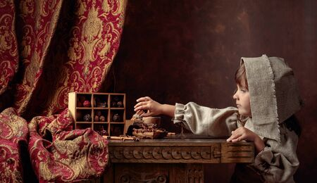 Little girl in an vintage linen dress near the table with sweets. Chocolate and spices on an old wooden table. Genre portrait in retro style.