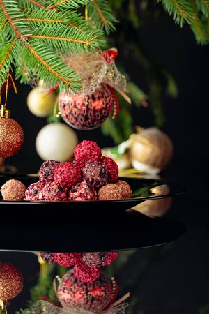 Various chocolate truffles on a black plate and Christmas tree.
