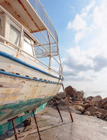 Old broken wooden ship on the seashore. Sunny summer day on a Mediterranean sea. Фото со стока