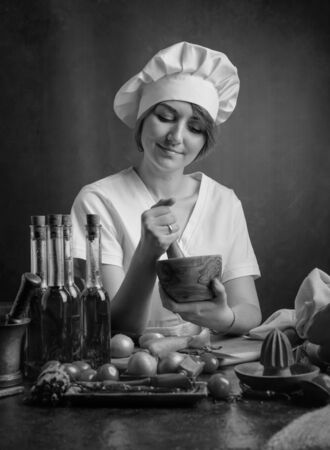 Young beautiful girl in a chef uniform with wooden mortar. On a table various kitchenware and vegetables. Reklamní fotografie - 130023520
